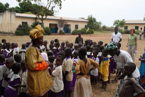 Kinder mit einer Lehrerin vor einem der beiden Schulgebäude